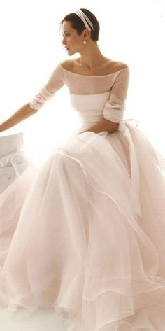 This is a unique wedding dress.  Love the sheer 3/4 sleeve top over the strapless gown, it gives the dress a really elegant vintage feel, and the floaty chiffon fabric.