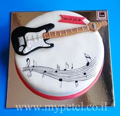 Standard round cake, decorated with a music theme and a fondant guitar on the top