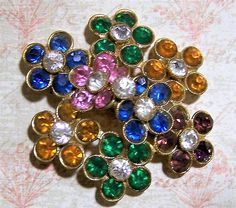 Vintage Art Deco multi color rhinestone brooch Green, purple, pink, blue, and yellow orange flowers all with crystal rhinestone centers Gold tone setting Signed Czecho 1 3/4 inches diameter Good vintage condition, shows no wear I do my best to only sell good quality vintage jewelry in good to great condition International buyers welcome, over charges are refunded Priority shipping is offered  Credit cards and Paypal accepted  Please visit my other pins: https://www.etsy.com&#x2...