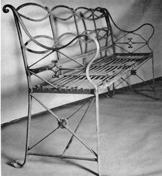 A Regency Wrought-Iron Bench: Made about 1810, the curved arms, back formed of two elements of serpentine curves, and the diamond-shaped and diagonal bracing members below the arms are decorative, reflecting this style as executed in wrought iron.