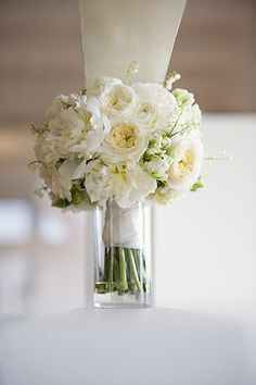The bridal bouquet will be a clutch bouquet of white peonies, ivory spray roses, green sage, and white lily of the valley wrapped in ivory ribbon with the stems showing.