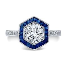 This stunning vintage European Cut stone is set in an octagon blue sapphire halo. Calibre cut sapphires accent a clean center diamond grasped by six prongs. Sparkling shank and intricate gallery complete this exquisite piece.  Center Stone: Diamond Weight: 1.20 ct. Color: I Clarity: VS2 Shape: European Cut  Side Stones: Sapphire Weight: 1.15 ct. Color: Blue Clarity: VS Shape: Calibre Cut