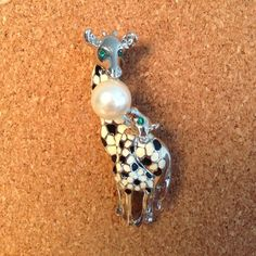 Giraffe and baby pin Black and white enameled giraffe pin featuring a large pearl. Green stones in he eyes of the mother giraffe and baby giraffe. A little over 2 inches long. .75 inches at its widest. Silver colored. Macy's Jewelry