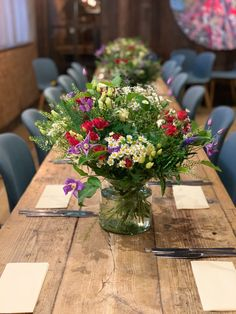 Low vases filled with flowers to create a summer meadow look on long tables