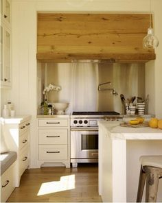 love the raw wood range hood in the creamy white kitchen.