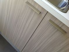 "Laundry - Our Colour Consultant chose for the cabinetry, Laminex Impressions in the Riven Finish ""Avignon Walnut."" (vertical grain) For the bench top, our Colour Consultant chose the Spark Finish ""Fresh Snow."""