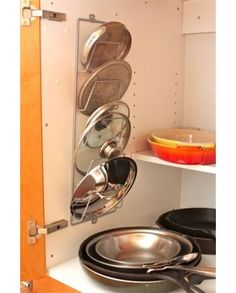 magazine rack mounted inside a cabinet to hold pot lids