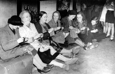 Women knit and talk in a tube station whilst sheltering from the blitz.