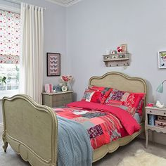 Neutral bedroom with pale blue walls, floral blinds, shabby chic furniture and pink patchwork quilt