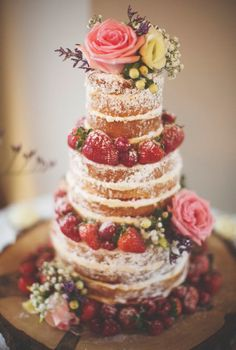 Tall naked wedding cake decorated with pink roses and strawberries fit for a garden wedding.
