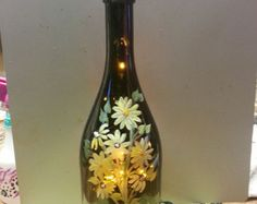 Dark Green wine bottle lamp with hibiscus, plumeria, & pansies. Message states, GROW where youre planted. This bottle lamp designed for a
