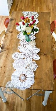 I love using old doilies to make a table runner, as long as they are stitched together.  Very creative.  Note they are not placed in a boring straight line.