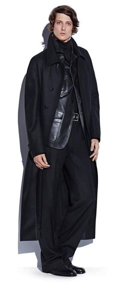 Model Marc André Turgeon pictured in a long black coat, layered over a black…