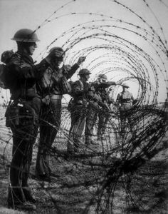 A barbed wire barricade is constructed by soldiers, as a precaution against a possible invasion by the Germans. (Photo by Fox Photos/Getty Images)