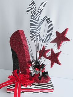 At Designs by Ginny wetook our custom Styrofoam high heeled shoe cutout and made it into a festive sweet 16 birthday table centerpiece. The red painted shoe with black heel, small mylar puffs atta...