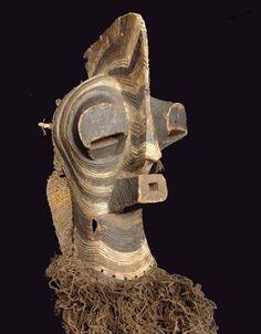 Masque Songye     : Zaïre     : Masque complet avec sont filet de portage et ses ornementations  Masque masculin dit Kifwébé utilisé lors des cérémonies d'initiations, de circoncisions et lors des funérailles. Au service de l'élite qui exerce le pouvoir, la crête a une signification de puissance dans la societé songye. Les couleurs et les incisions géométriques symbolisent la magie positive pour le blanc et le noir pour la sagesse.