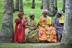 Suriname, Paramaribo. Creole women in Kotomisi dress,  the national  creole costume, in the Palm Garden.