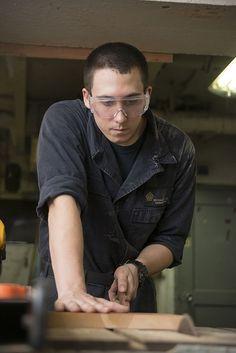 Hull Maintenance Techician Fireman Michael Lloyd cuts wood to craft door plaques in the carpentry shop aboard the aircraft carrier USS Dwight D. Eisenhower (CVN 69).