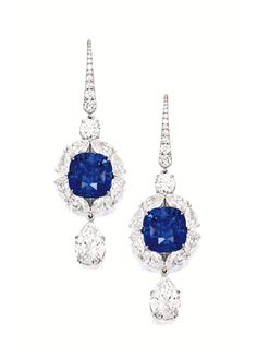 PAIR OF SAPPHIRE AND DIAMOND PENDENT EARRINGS. Each suspending on a cushion-shaped sapphire weighing 8.90 and 7.86 carats, surrounded by pear-shaped diamonds altogether weighing approximately 6.00 carats, surmounted by an inverted pear-shaped diamond each weighing 2.02 carats, mounted in 18 karat white gold.