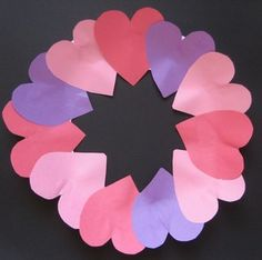 """Begin by cutting the center out of the paper plate to create the framework for the wreath. (I find it's easier to use a steak knife to make a small slit in the plate before using scissors.) Then cut a total of twelve hearts about 2"""" wide from the red, pink and purple construction paper. Finally, glue the hearts around the front of the paper plate so they slightly overlap."""
