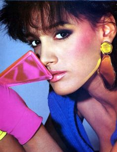 1980s Hair and Makeup.  Heavy blush all the way to hairline, rimmed eyes, shinny lips.  Her hair looks to be a female mullet.  Possibly Jennifer Beals?  Or perhaps just a similar looking model.