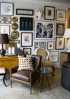 Gallery wall living room with an eclectic mix of black and white and sepia photos and prints, as well as interesting objects like a white rams head and naturalist framed butterfly specimens. This art wall has a very Cabinet of Curiosities look - Gallery Wall Ideas & Decor