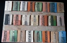 Tracey Broome : Sig and Stain. Test tiles are out of the bisque, I have put some black iron oxide wash on them and they will go back in for an 04 firing. They are chrome oxide, red iron oxide, cobalt carbonate, copper carbonate and rutile colored terra sigs and washes.