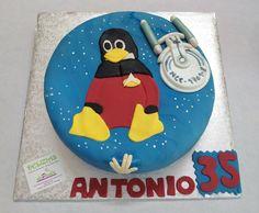 Para Antonio, fanático de Linux y de las saga de Star Trek, nos han encargado elaborar esta divertida tarta en fondant de la nave y el famoso pingüino. Un bizcocho de vainilla, relleno de nata y frambuesa, y cubierto en fondant azul. La nave esta modelada en fondant y el pingüino esta elaborado con la técnica puzzle.