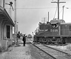 The Southern Pacific local is on its way, and Missouri Pacific's Texas Eagle will soon be moving again following a lengthy delay at the depot in McNeil, Texas. So ends another typical incident in everyday railroading during August 1965. Fortunately, experienced railroaders can wave it off. Photograph by J. Parker Lamb