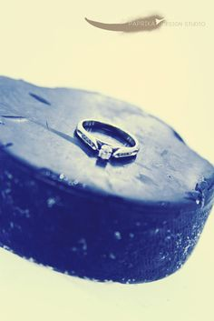 Engagement ring on the hockey puck. had to chase my husband around the Ice Rink to get mine from him, ha ha ha had to work for it!!