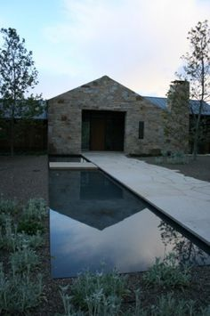 """Amazing use of a narrow space! This lap pool doubles as a water feature surrounded by Mediterranean perennials and native stone. A """"floating"""" footbridge connects the entry walk to the rest of the landscape and creates a magical illusion for anyone crossing the water."""