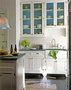 White cabinets with a dark tile floor.