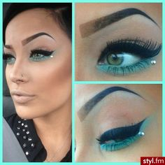 Defined black cat-eye eyeliner with teal shadow and a single crystal accent.
