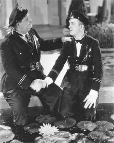 Oliver Hardy and Stan Laurel in The Midnight Patrol shaking hands as cops Poster Laurel And Hardy, Stan Laurel Oliver Hardy, Great Comedies, Classic Comedies, Classic Movies, Rl Burnside, Sound Film, Comedy Duos, Blue Raincoat