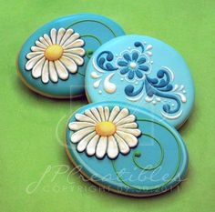 cookie icing: Dainty daisies on blue background .. big daisies in white with yellow center ... tole painting design in dark blue and white on pale blue ...
