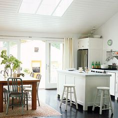 Cottage kitchen  Oversize windows and skylights invite in the sunshine. Walls are painted a light-bouncing white, while white ceramic subway tiles brighten the kitchen and baths.  For contrast, the wooden floors are stained in a custom mix of ebony and dark walnut shades; the high-gloss polyurethane top coat reflects even more light.  Get the look: Wall paint is Decorator's White eggshell with semi-gloss trim throughout (benjaminmoore.com for stores) Kitchen tile  is ceramic 3- by…