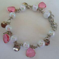 Pulseira branca feita com contas acrílicae coração acrílico rosa e pingentes prateado. R$ 4,50