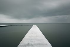 I recently stumbled across Waterscapes, a series by Hungarian photographer Akos Major. The series features a collection of photographs capturing ominously still  bodies of water. The minimal composition matched with the eerie static water begins to create a surreal environment out of reality. The muted tones of this environment work to compliment the minimal structures he interjects into the waterscapes, giving the viewer a point of departure, as well as something to hold on to as one loses…