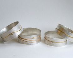 Hammered sterling silver bangles with 18 carat gold details and rose cut cinnamon diamonds.