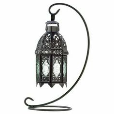 """Cast a warm glow in your sunroom or breakfast nook with this iron candle lantern, showcasing a Moroccan-inspired design and scrolling stand.     Product: Candle lanternConstruction Material: Iron and glassColor: Black and clearFeatures: Scrolling stand Moroccan-inspired design Accommodates: (1) Candle - not includedDimensions: 15"""" H x 6.75"""" W x 7.75"""" D"""