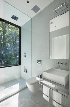 Modern white bathroom with natural lighting    New Canaan Residence by Specht Harpman