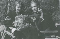 Original, vintage photo of Jeanette MacDonald and Nelson Eddy on the set of Rose Marie ( MGM 1936). This pose is slightly different than the one in Sharon's book. Here, Jeanette is looking directly at the camera and her right hand is holding the flowers.We can see that the overcoat she is wearing has the RCMP insignia. Nelson must have offered it to her to keep her warm as she was always cold. As in the other pose, Nelson is looking back at her adoringly - ESCANO COLLECTION