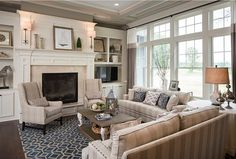 Family Room feels sophisticated and also very cozy, with its navy blue accents.  The fireplace surround is 12x12 Cardinal Beige marble tile.   Beautiful Family Home with Open Floor Plan