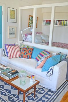 I love this. I think I can recreate this set-up with three open white bookshelves in between my bed and TV stand and stool, though it won't be as open as this looks. Also, love the colors!