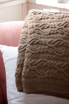 In this textured afghan, cables twist and weave together to form an elaborate motif reminiscent of the traditional sweaters of the Aran Islands.
