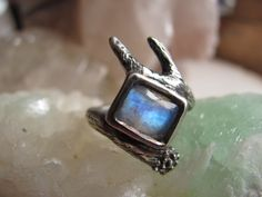 A flashy rectangular moonstone is harnessed by a hand carved deer antler. This piece is solid sterling silver and made entirely by hand from start to finish. This ring is US size 5.75 but may fit up to a size 6. We have added a patina to the silver then polished it up to best reveal its intricate t