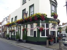 Beautiful corner pub/tavern/restaurant showing a superb example of what hanging flowers and planter boxes and potted plants can add to your curb appeal!  Love it!!