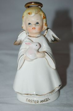 """A very sweet Easter ceramic angel figurine made by Lefton  She's holding an Easter bunny.  She's in very good vintage condition with some light crazing, and she could use a bath. No chips, cracks or repairs. She's approx 5"""" tall and 2 1/4"""" wide, and has a Lefton sticker on the bottom. This is from my vintage Easter collection which I'm thinning out a bit. Please check the photos for further details, and ask any questions before bidding. I'm listing othe..."""