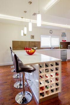 une cuisine moderne avec des meubles blancs et des casiers de vin sous une table haute