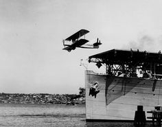 A DT-2 launches from the carrier Langley (CV 1) moored at Naval Air Station (NAS) San Diego, California, in a test to determine the feasibility of using flush-deck catapults to launch wheeled aircraft from ships. This image was taken on April 2, 1925